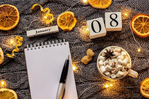Composizione invernale. calendario in legno 8 gennaio tazza di cacao con marshmallow, blocco note aperto vuoto con penna