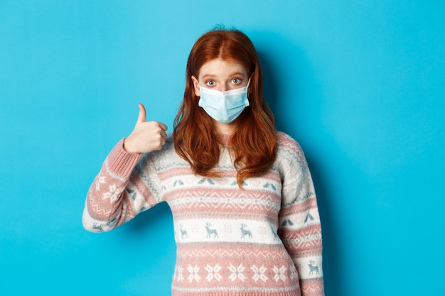 Inverno, coronavirus e concetto di distanza sociale. ragazza rossa impressionata in maschera facciale, mostrando il pollice in su in segno di approvazione, come e lode, in piedi su sfondo blu