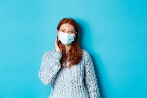 Inverno, covid-19 e concetto di allontanamento sociale. bella ragazza adolescente dai capelli rossi, indossa una maschera per il viso e infila una ciocca di capelli dietro l'orecchio, fissa la telecamera, in piedi su sfondo blu.