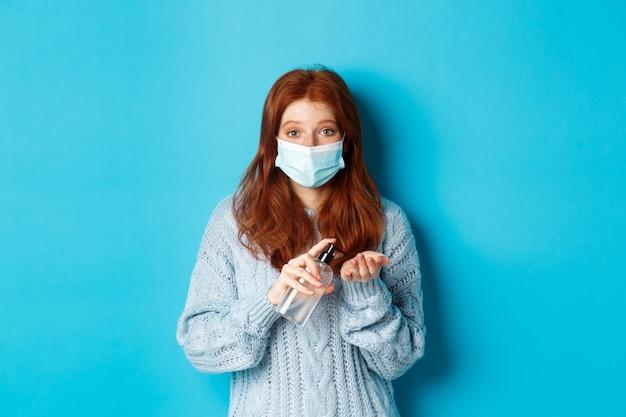 Inverno, covid-19 e concetto di allontanamento sociale. giovane donna soddisfatta della testarossa nella maschera facciale che mostra i gesti giusti e giusti e guardando a sinistra promozionale, sfondo blu.