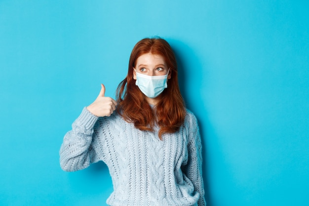 Inverno, covid-19 e concetto di allontanamento sociale. giovane donna soddisfatta della testarossa in maschera facciale che mostra bene, pollice in alto gesto e guardando a sinistra promo, sfondo blu.