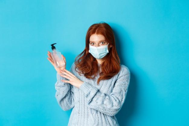 Inverno, covid-19 e concetto di allontanamento sociale. giovane ragazza rossa in maschera facciale che mostra disinfettante per le mani, dimostrando antisettico per la disinfezione, in piedi su sfondo blu.