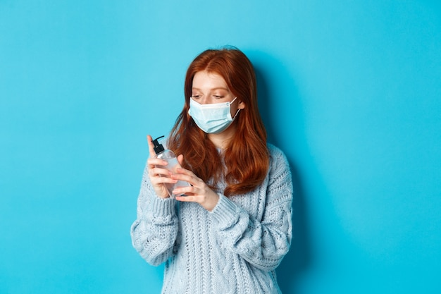 Inverno, covid-19 e concetto di allontanamento sociale. giovane donna rossa in maschera per il viso mani pulite con antisettico, disinfettando con disinfettante per le mani, in piedi su sfondo blu.