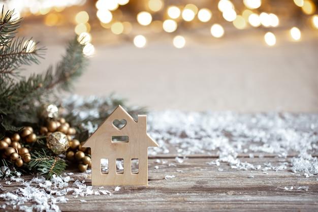 Dettagli di decorazioni festive invernali accoglienti, neve su un tavolo di legno e bokeh. il concetto di un'atmosfera festosa a casa.
