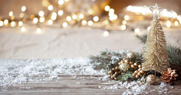 Parete accogliente invernale con dettagli di decorazioni festive, neve su un tavolo di legno e bokeh. il concetto di un'atmosfera festosa a casa.