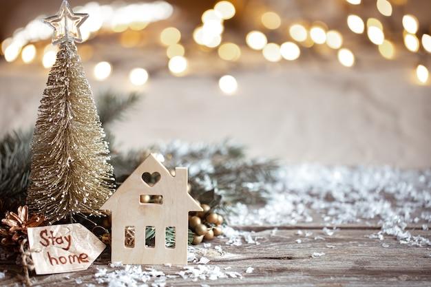 Parete accogliente invernale con dettagli di decorazioni festive, neve su un tavolo di legno e bokeh. rimanere a casa concetto.