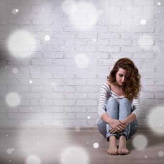 Depressione invernale e solitudine - donna infelice seduta sul pavimento su un muro di mattoni bianchi