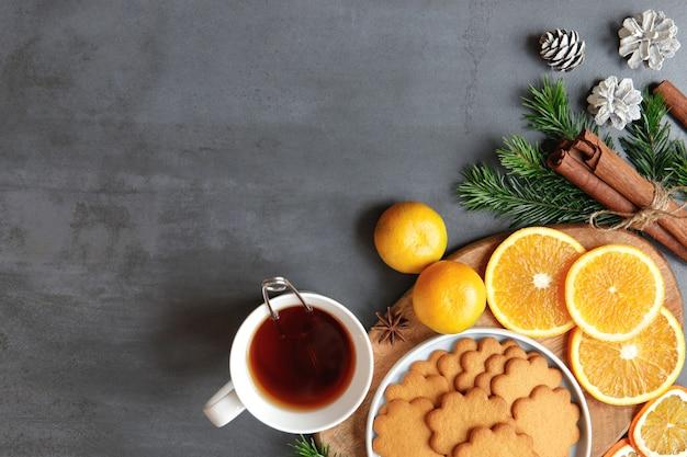 Bevanda invernale. lay piatto di tazza bianca con tè caldo con colino da tè, biscotto di pan di zenzero, bastoncini di cannella, coni, rametti di abete rosso, mandarino, fette di arancia, anice su sfondo nero.