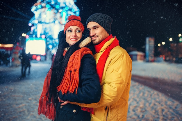Serata invernale di amore coppia all'aperto, illuminazione natalizia. uomo e donna che hanno incontro romantico sulla strada della città con le luci