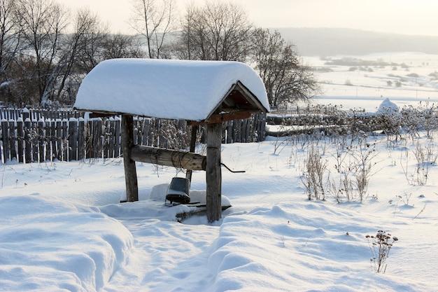 Fiaba invernale nel villaggio con tetti coperti di neve, pozzi