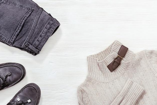 Inverno, autunno abbigliamento femminile. mocassini in pelle nera, jeans scuri e pullover grigio chiaro su fondo di legno bianco con spazio di copia. disteso.