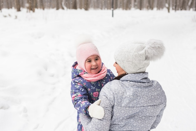 Concetto di inverno, famiglia e infanzia - la madre sta camminando con sua figlia nel bosco innevato e