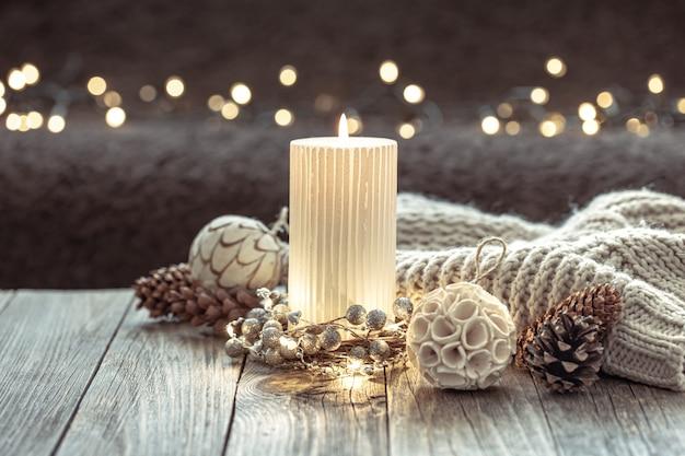 Sfondo festivo invernale con candela accesa e dettagli di decorazioni per la casa su sfondo sfocato con bokeh.