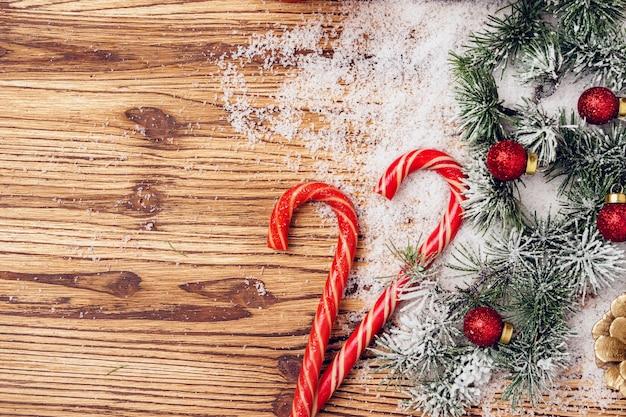 Sfondo festivo invernale con rami di abete e bastoncini di zucchero