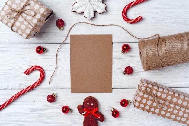 Sfondo festivo invernale con omino di pan di zenzero e bastoncini di zucchero sul bordo di legno bianco, piatto laici