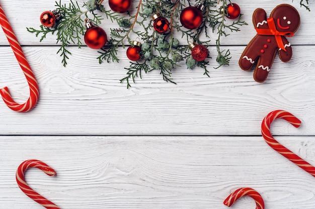 Sfondo festivo invernale con omino di pan di zenzero e bastoncini di zucchero sul bordo di legno bianco, l copia spazio