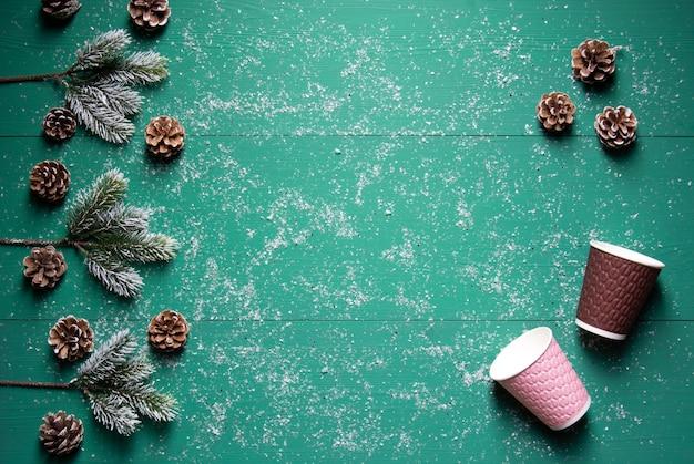 Inverno festivo concetto coni rami di abete bicchieri di carta colorati sul tavolo di legno verde