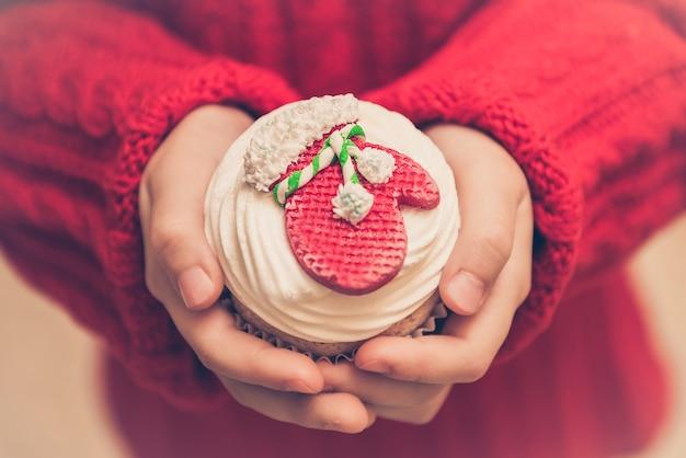 Cupcake festivo invernale con un guanto rosso che tiene