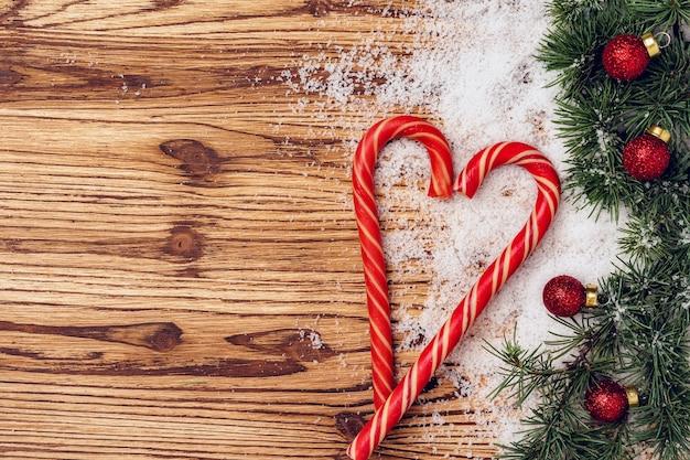 Inverno festivo con rami di abete, neve e bastoncini di zucchero sulla tavola di legno