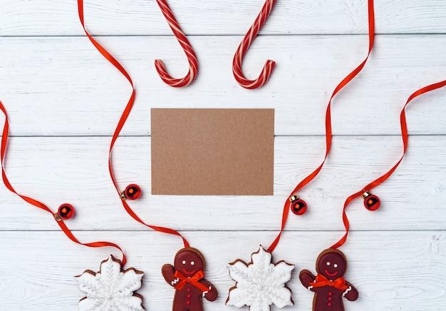 Inverno festivo con omino di pan di zenzero e bastoncini di zucchero sul bordo di legno bianco