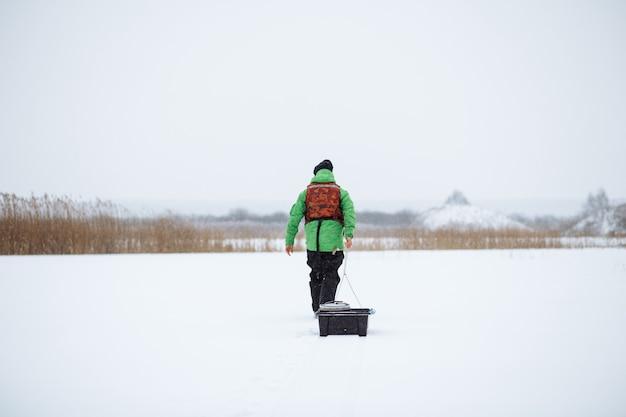 Pescatore invernale sullo sfondo di un giovane cammina su un lago innevato con una slitta