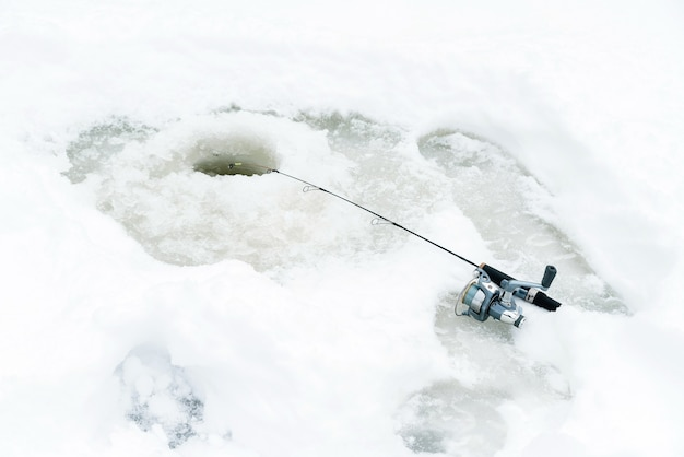 Pesca invernale sul ghiaccio, esche oscillanti in un buco nel ghiaccio.