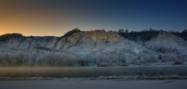 Mattina gelida invernale prima dell'alba. fiume gelido dalle rive collinari e grandi banchi di ghiaccio.