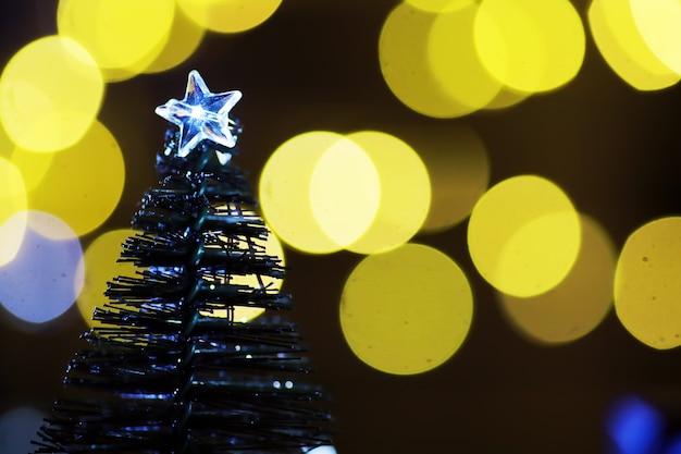 Sfondo vacanza invernale con luci glitter abete congelato bokeh