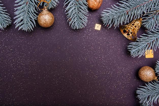 Concetto festivo della carta della decorazione di vacanza invernale: alberi di natale, campane e palle su fondo nero con lo spazio della copia