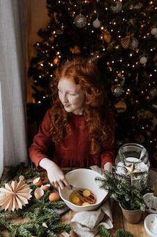Durante una vacanza invernale, una ragazza dai capelli rossi mescola uova e zucchero in una ciotola.