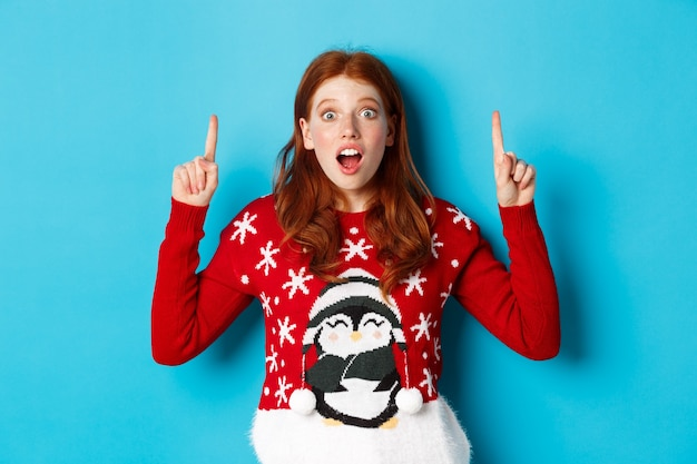 Vacanze invernali e concetto di celebrazione. ragazza rossa stupita che mostra pubblicità, indicando il logo di natale, in piedi eccitato su sfondo blu.