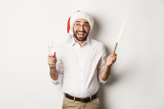 Vacanze invernali e celebrazione. felice imprenditore godendo la festa di capodanno, indossando il cappello di babbo natale e bevendo champagne, sorridente divertito, sfondo bianco.