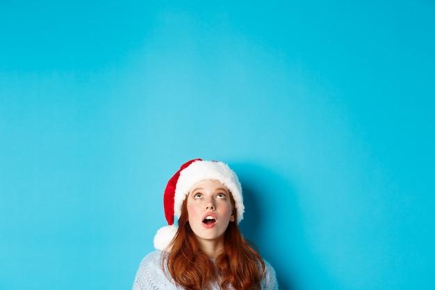 Vacanze invernali e concetto di vigilia di natale. testa di bella ragazza rossa con cappello santa, appare dal basso e guarda il logo, vedendo l'offerta promozionale stupita, sfondo blu.