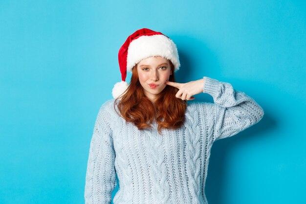 Vacanze invernali e concetto di vigilia di natale. impertinente ragazza adolescente con i capelli rossi, indossa un cappello da babbo natale, si gode il nuovo anno, si tocca la guancia e guarda fiduciosa alla telecamera.