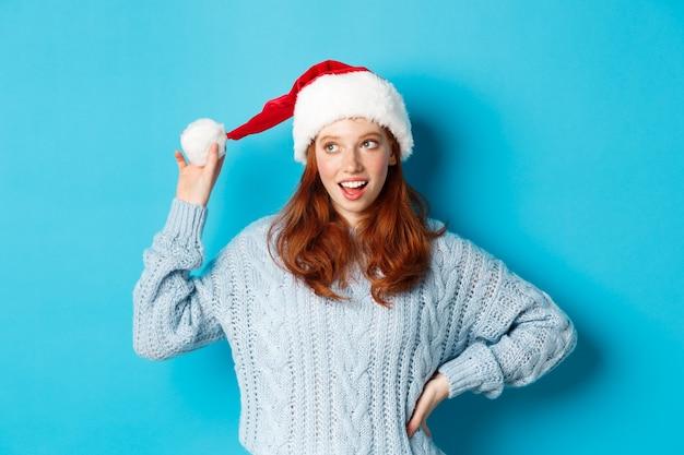 Vacanze invernali e concetto di vigilia di natale. stupida ragazza rossa con le lentiggini, toccando il suo cappello da babbo natale e pensando, pianificando la celebrazione del nuovo anno, in piedi su sfondo blu.