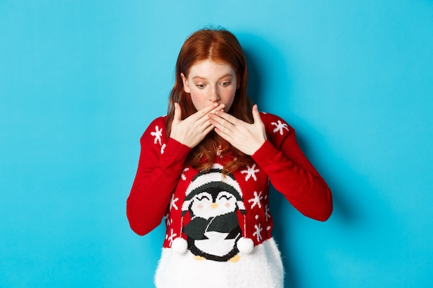 Vacanze invernali e concetto di vigilia di natale. ragazza rossa sorpresa ansimante, guardando in soggezione, fissando il logo, in piedi in maglione di natale su sfondo blu.