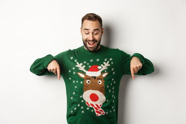 Vacanze invernali e natale. uomo barbuto felice in maglione verde, guardando e puntando le dita verso il basso verso la pubblicità, mostrando lo spazio della copia, sfondo bianco