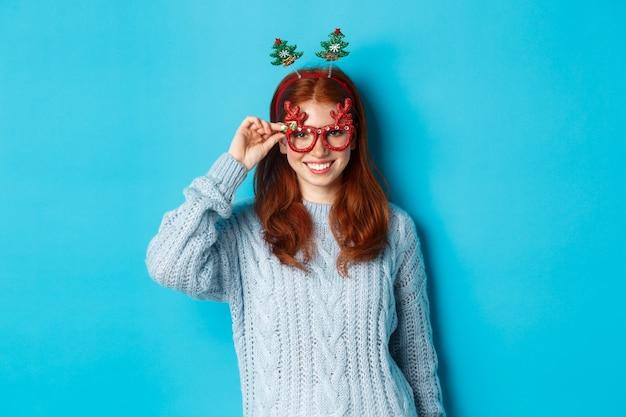 Vacanze invernali e concetto di vendite di natale. modello femminile bella rossa che celebra il nuovo anno, indossando la fascia e gli occhiali divertenti del partito, sorride alla macchina fotografica.