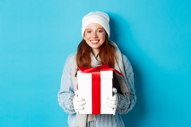 Vacanze invernali e concetto di vendita di natale. cute redhead teeanage girl in beanie, sewater e sciarpa tenendo il regalo in scatola avvolta, sorridente, augurando buon natale, in piedi su sfondo blu.