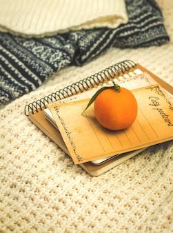 Decorazione del concetto di casa invernale, composizione invernale o autunnale in vacanza, mandarini su libri e foto di cartoline