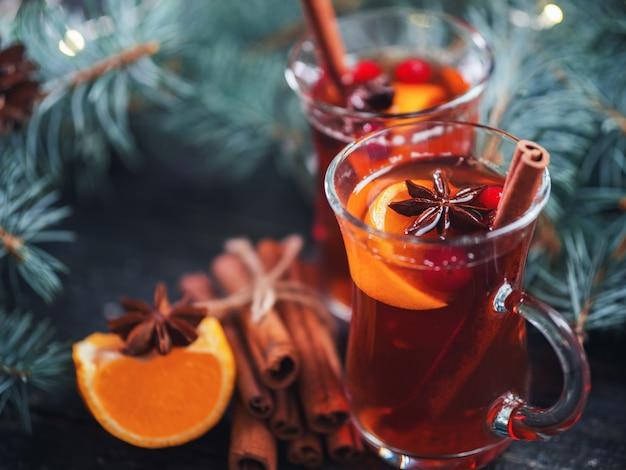 Bevanda calda invernale vin brulé natalizio in bicchieri con anice, cannella e mandarino