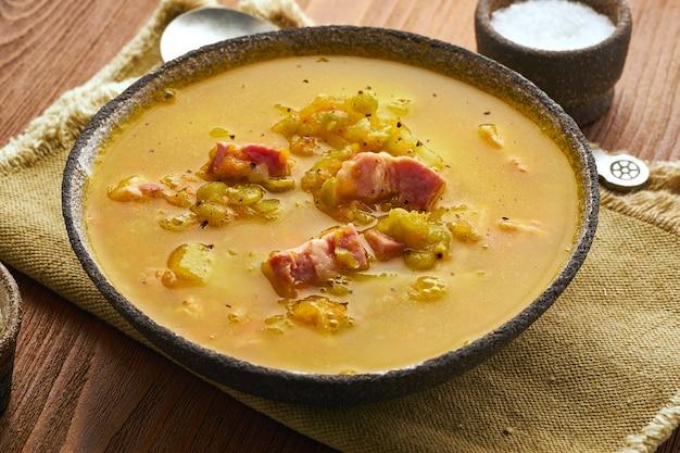 Zuppa calda invernale con piselli tritati, carne di maiale, pancetta affumicata, affumicato sul tavolo di legno marrone scuro