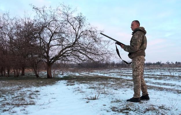 Caccia invernale. cacciatore in movimento con fucile e in cerca di preda.