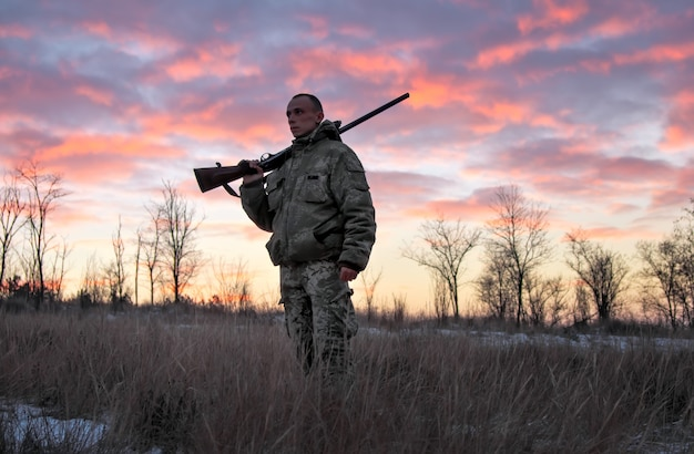 Caccia invernale all'alba. cacciatore in movimento con fucile e in cerca di preda.