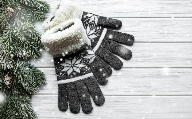 Guanti invernali lavorati a maglia su una superficie di legno vicino a rami di abete
