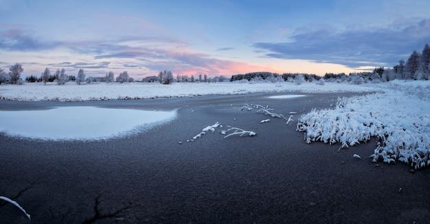 Lago d'inverno coperto di ghiaccio e neve al tramonto. west lothian, scozia, regno unito