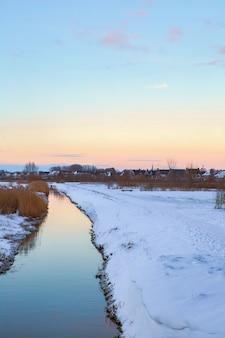 Paesaggio invernale nei paesi bassi con bel cielo colorato al tramonto e fresca neve bianca