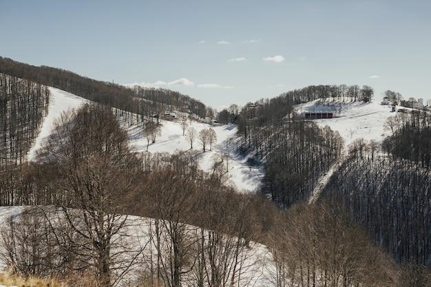 Paesaggio invernale della montagna innevata, cielo blu e stazione sciistica in italia alpi, europa.
