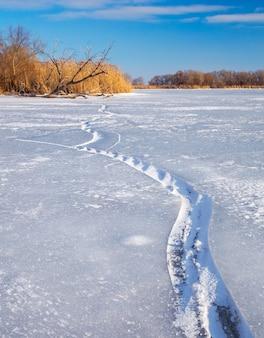 Paesaggio invernale con crepe, intoppo, canne e fiume ghiacciato