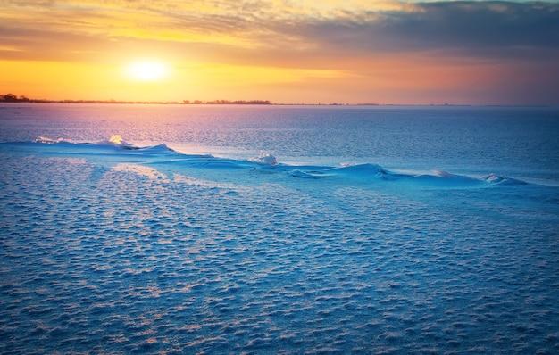 Paesaggio invernale con lago ghiacciato, crepe e cielo al tramonto.